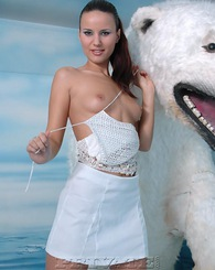 Pretty glamorous sexy girl in white posing with polar bear
